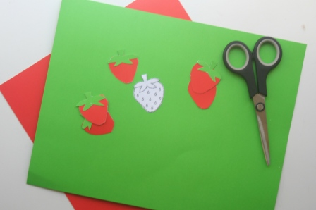 Cut out strawberries using red and green craft paper and a stencil you can find online.